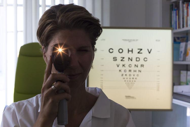 Portrait of mid adult woman holding eye testing equipment