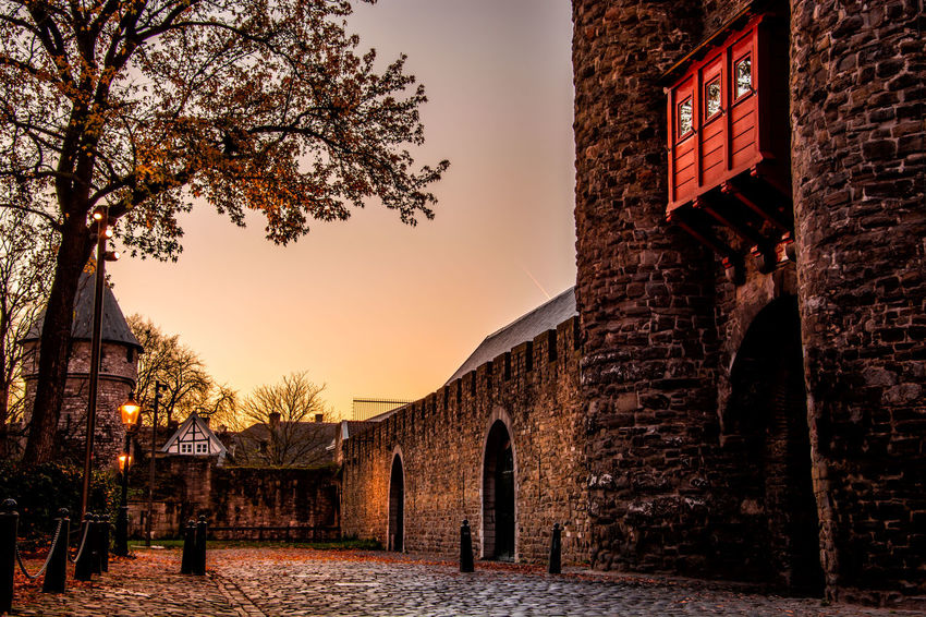 """Helpoort (""""Hell's Gate""""), an imposing gate with two towers, built shortly after 1230, the oldest city gate in the Netherlands Architecture Architecture Built Structure City Cityscapes Cobblestone Day Hell's Gate Helpoort Historic History Holland Limburg Maastricht No People Outdoors Red Sky Stad Sun Sunlight Sunset Sunset_collection Sunshine Warm"""