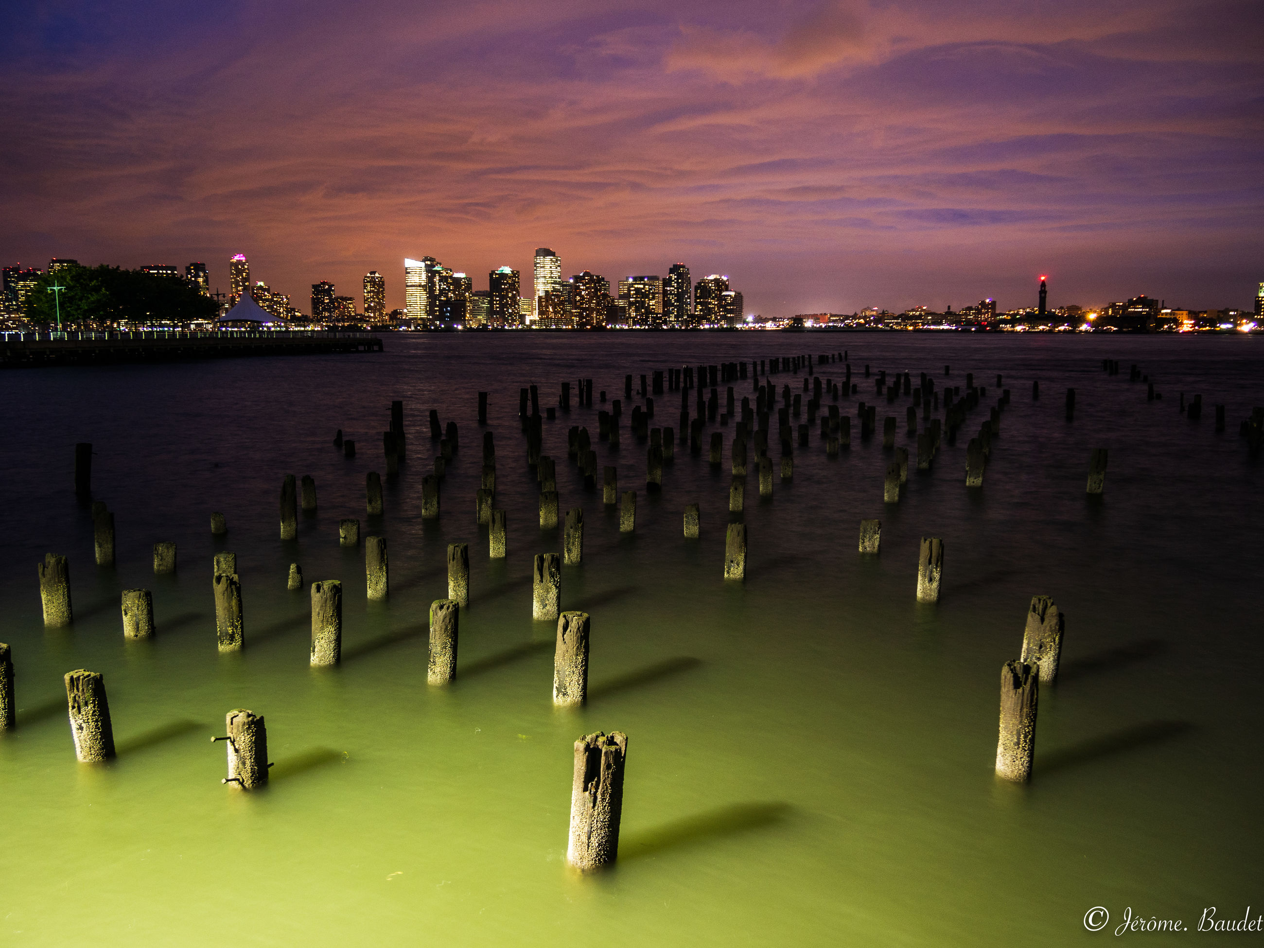 water, architecture, sky, built structure, sunset, building exterior, nature, waterfront, sea, city, no people, building, cloud - sky, office building exterior, illuminated, urban skyline, post, skyscraper, scenics - nature, wooden post, outdoors, cityscape