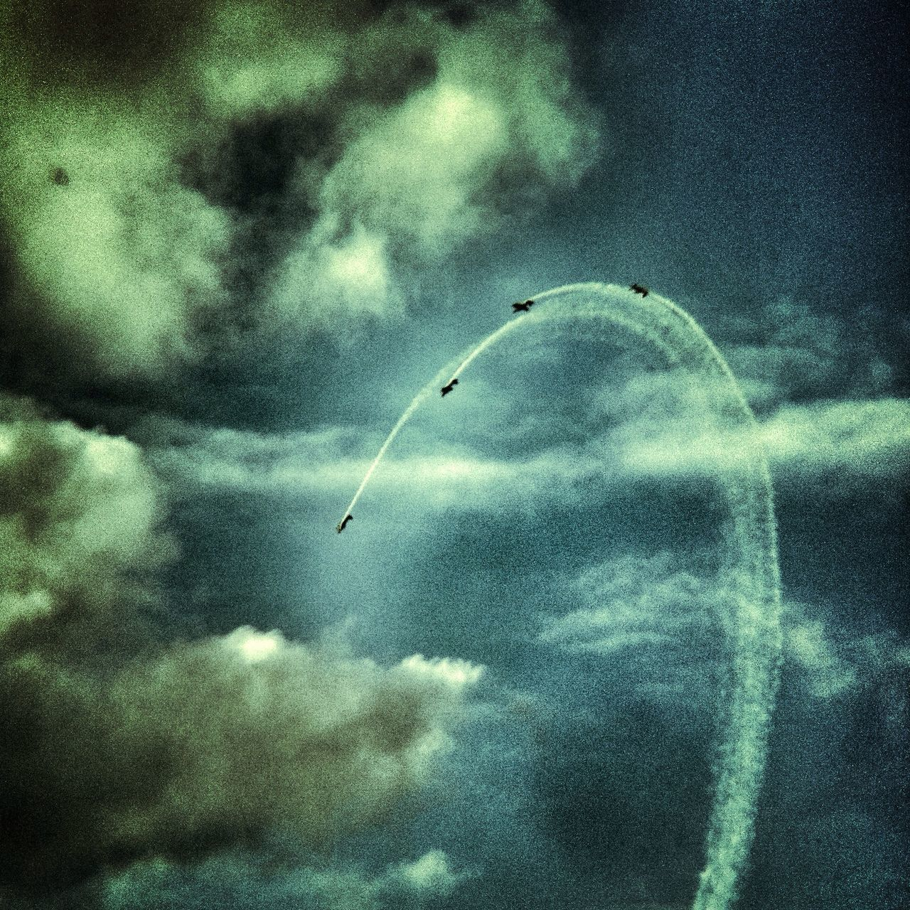 Low angle view of air show against cloudy sky