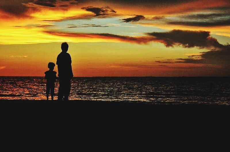 Silhouette friends on beach against dramatic sky during sunset