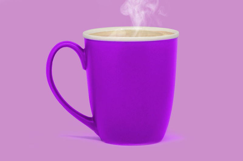 Close-up of tea cup against pink background