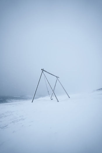 View of swing on snow covered land against sky