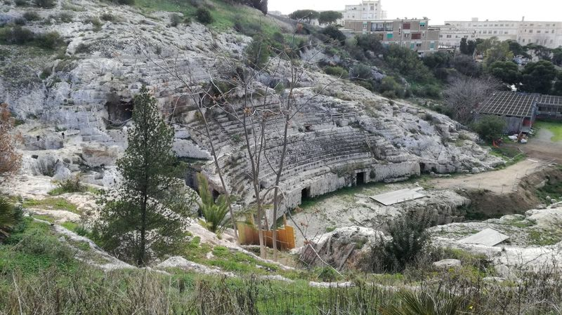 https://en.m.wikipedia.org/wiki/Roman_Amphitheatre_of_Cagliari Ancient History Old Anphitheater Ancient Architecture High Angle View Outdoors Day Building Exterior Built Structure Tree No People Beauty In Nature City Rock - Object Nature