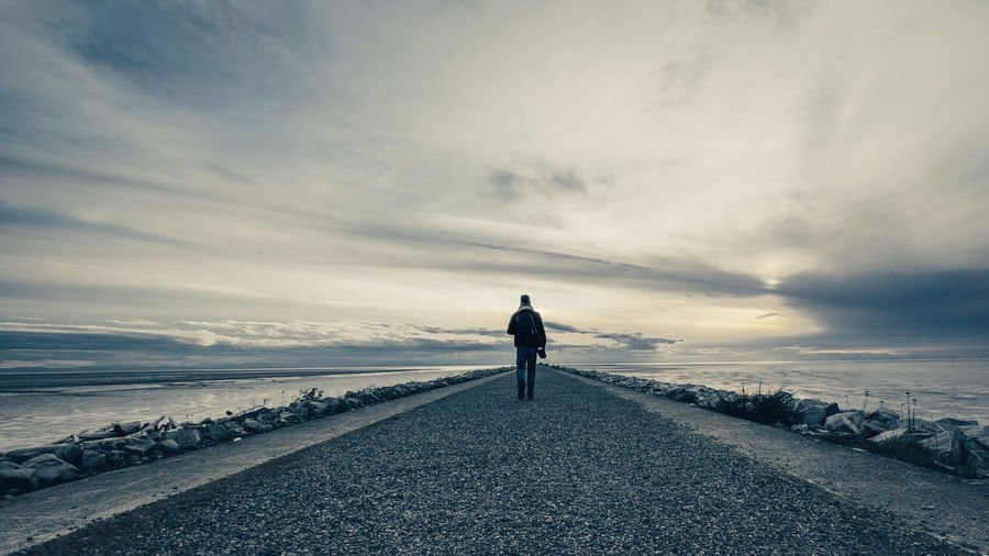 Rear view of man standing on shore against sky during sunset