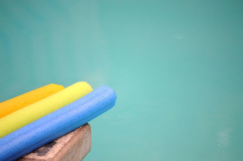 Close-Up Of Colorful Sponge By Colored Background