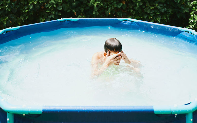 Rear view of shirtless boy in swimming pool