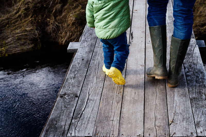 Low section rear view of people walking on wooden footbridge over river