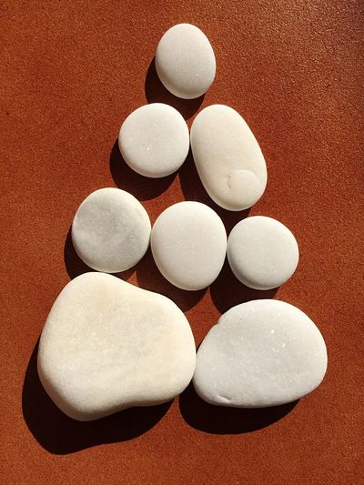 High angle view of pebbles arranged on brown surface