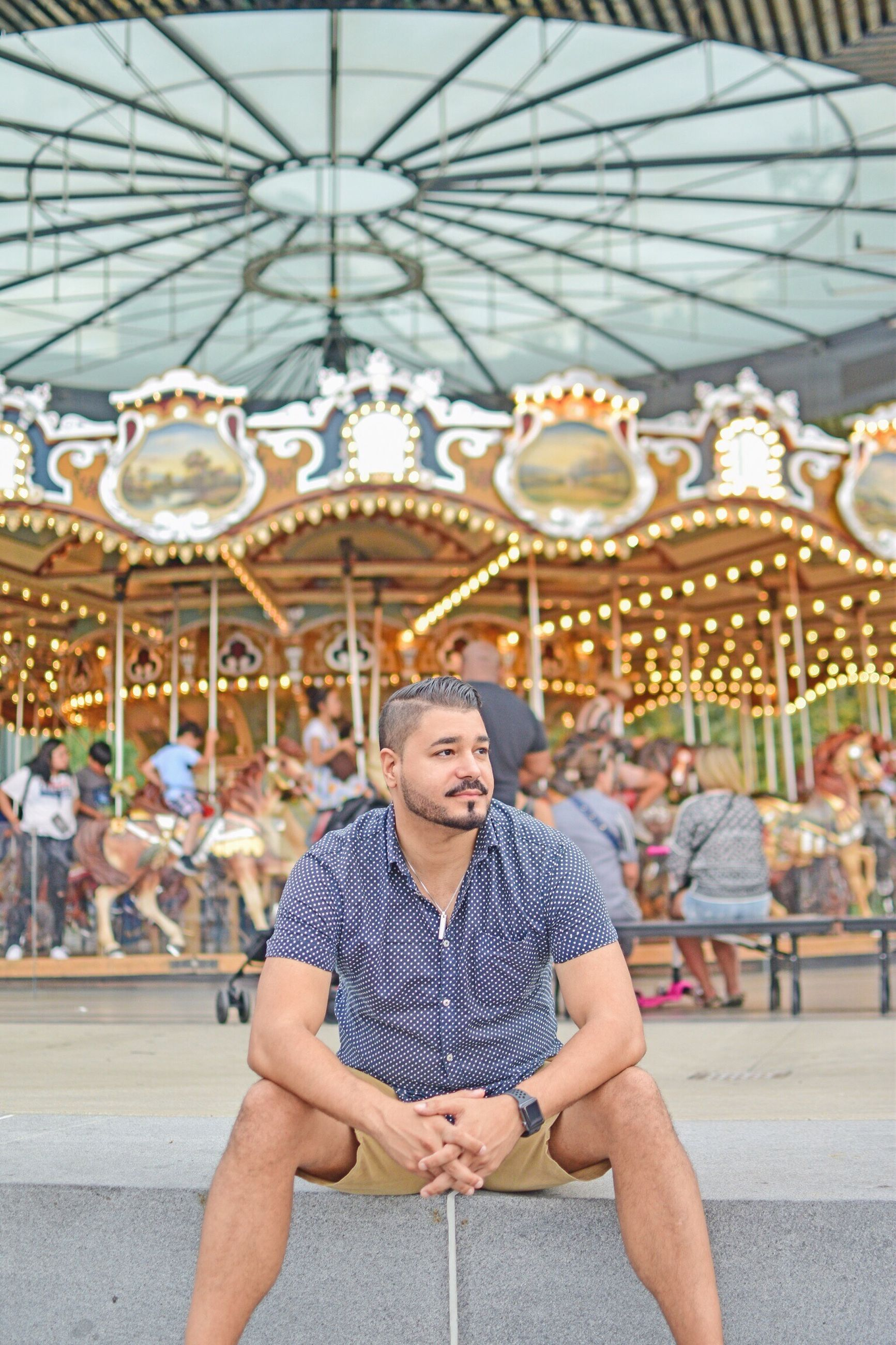leisure activity, amusement park, amusement park ride, one person, arts culture and entertainment, focus on foreground, incidental people, front view, real people, lifestyles, portrait, young adult, enjoyment, adult, sitting, day, casual clothing, young men, carousel
