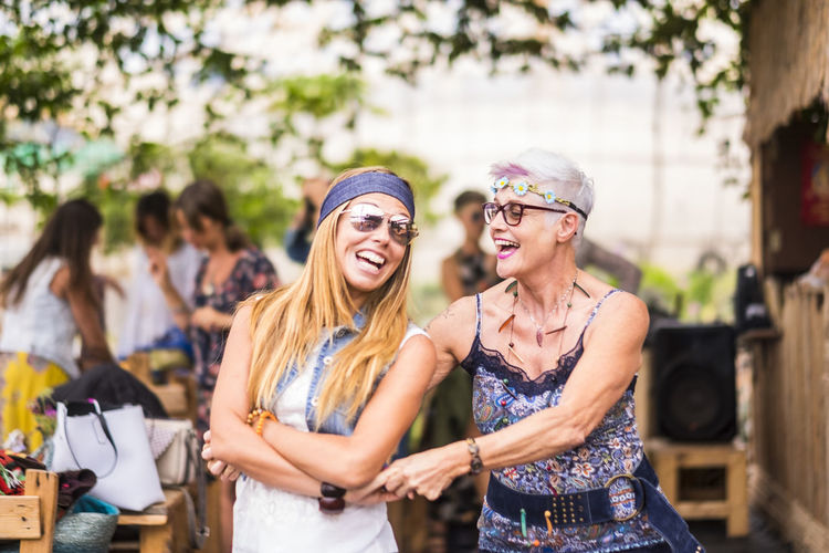 happy friendship couple of woman young and mature ladies with hippy clothes and dress have fun together dancing and hugging each other. beautiful adults enjoying a colored festival Females Adult Casual Clothing Caucasian Day Emotion Enjoyment Fashion Friendship Fun Glasses Hairstyle Happiness Leisure Activity Lifestyles Music Festival Outdoors Real People Smiling Sunglasses Togetherness White Hair Women Young Adult Young Women