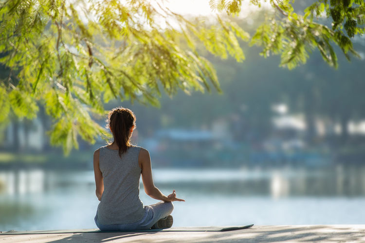 The back of a beautiful woman Yoga practice near the pool. At sunrise Beauty In Nature Day Healthy Lifestyle Lake Lifestyles Lotus Position Nature One Person Outdoors People Real People Relaxation Scenics Sitting Tranquil Scene Tree Water Women Yoga Young Adult Young Women