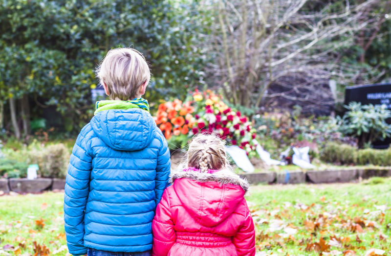 Siblings standing against flowers in graveyard