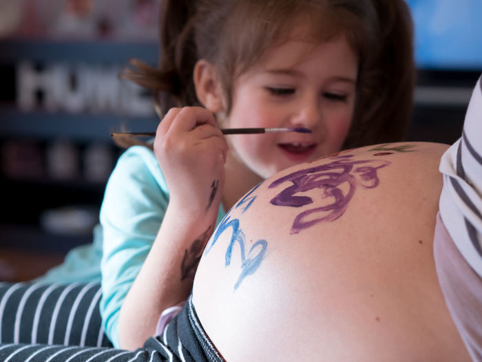 Small girl painting mothers belly and smiling at home Fun Home Mother Stomach Art And Craft Belly Child Childhood Close-up Color Creativity Daughter Drawing Girls Human Hand Indoors  Leisure Activity Lifestyles Mom Painting People Pregnancy Pregnant Real People Two People