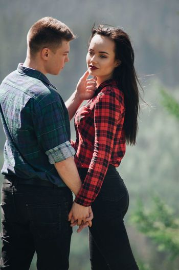 Stylish young hipster couple in love in the mountains. Two People Love Togetherness Men Positive Emotion Couple - Relationship Bonding Emotion Young Men Standing Heterosexual Couple Three Quarter Length Young Adult Casual Clothing Young Women Focus On Foreground Real People Leisure Activity Women Outdoors Care