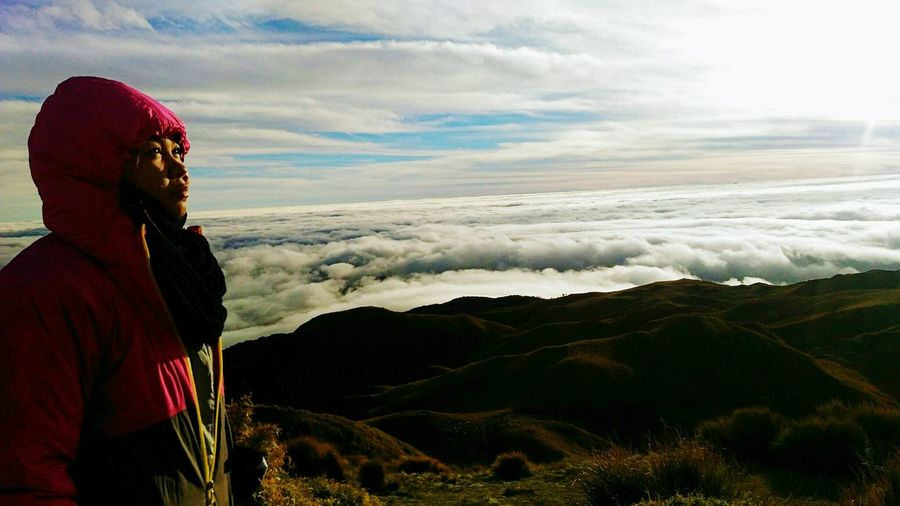 Woman standing on mount pulag against cloudy sky
