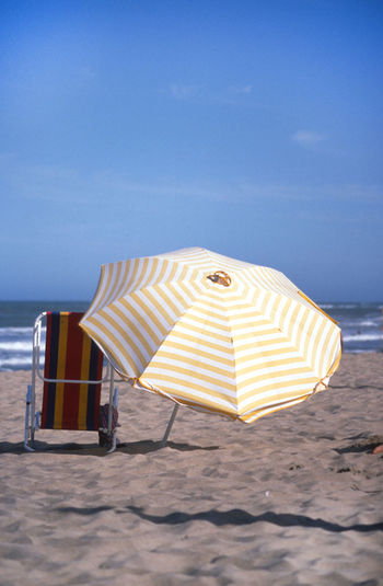 Beach Beach Umbrella Beauty In Nature Blue Chair Day Horizon Over Water Land Nature No People Outdoors Parasol Sand Sea Shade Sky Striped Summer Tranquility Umbrella Water