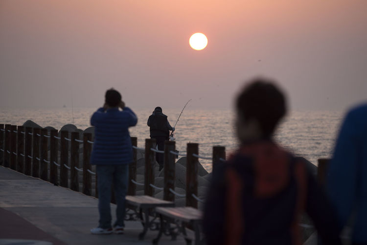 People on pier at beach during sunset