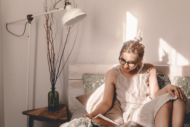 Woman reading book while sitting on bed at home