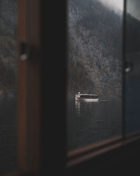 Boat sailing on sea seen through window