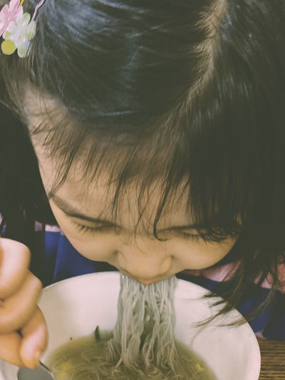 High angle view of girl eating noodles