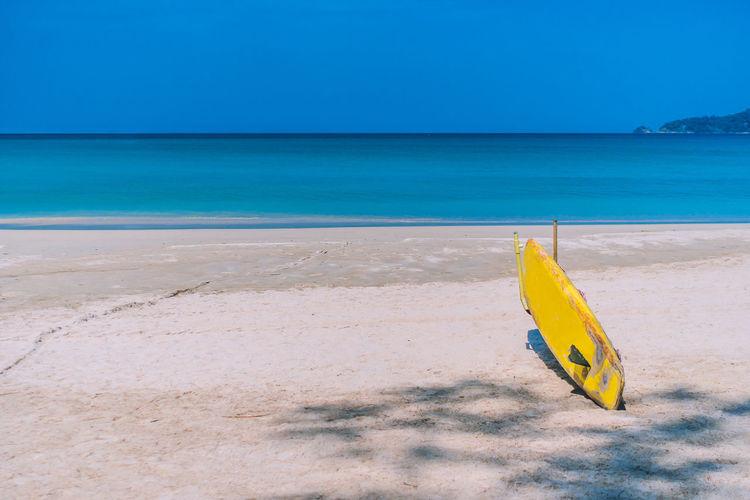 Yellow umbrella on beach against blue sky