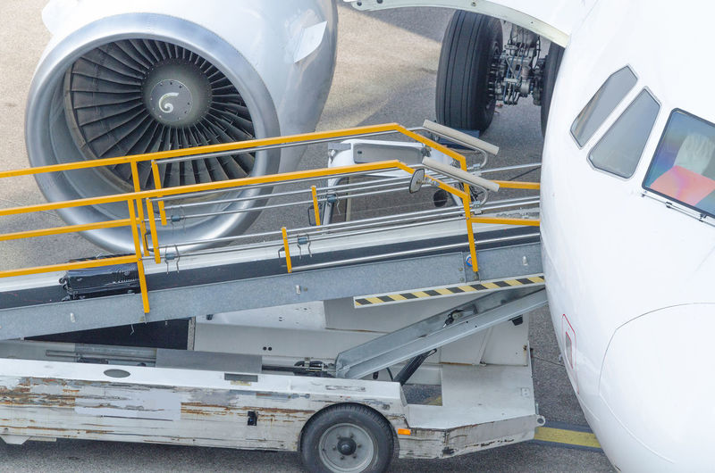 High angle view of passenger boarding bridge by airplane at airport