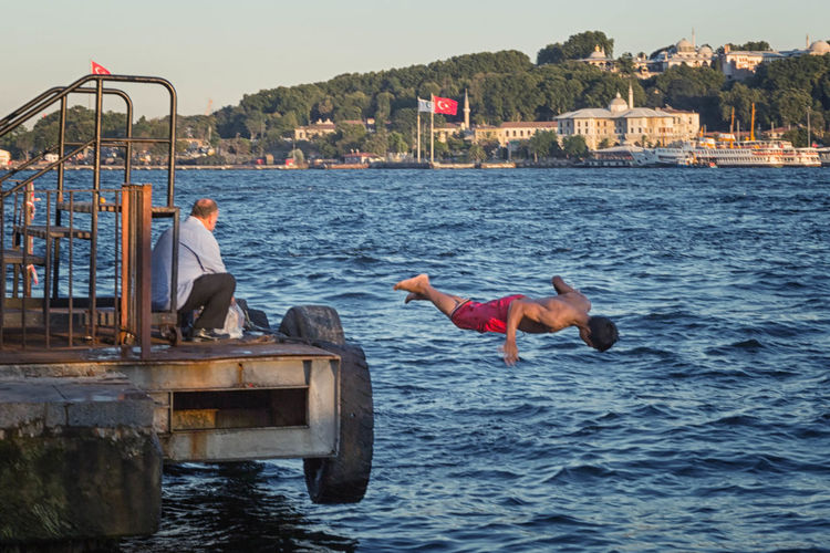 Diving In Blue Boat Bosphorus Boy, Man, Lad, Built Structure Day Diver Diving In  Dock, Docks, Blue, In The Air Istanbul, Turkey, Bosphorus, Sea, Europe, European, Asia, Asian, Country, Golden Horn, Bosphorus, Bosphorous Straights, Karaköy Leisure Activity Lifestyles Nature Outdoors Rippled Sky Swim Tourism Vacations Water Waterfront