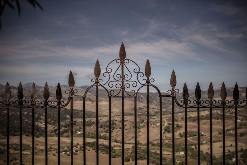 Metallic fence on land against sky