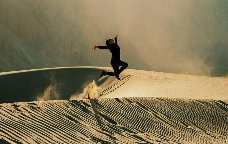 Full length of man jumping at desert