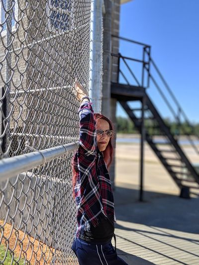 Portrait of young woman standing against chainlink fence