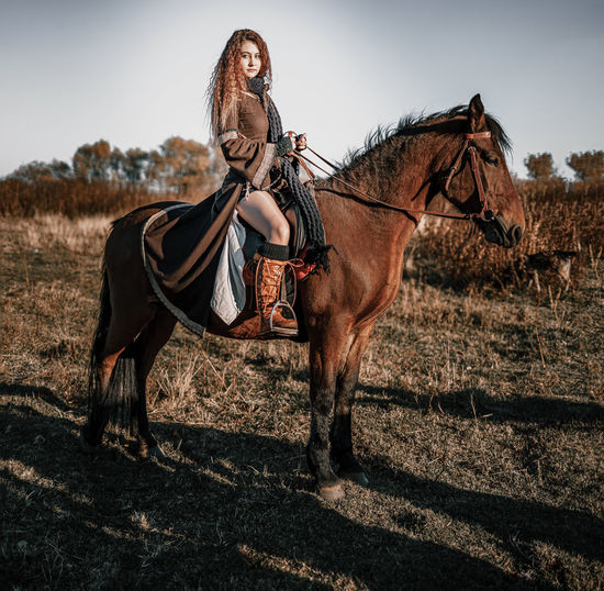 Full length portrait of young woman riding horse on field