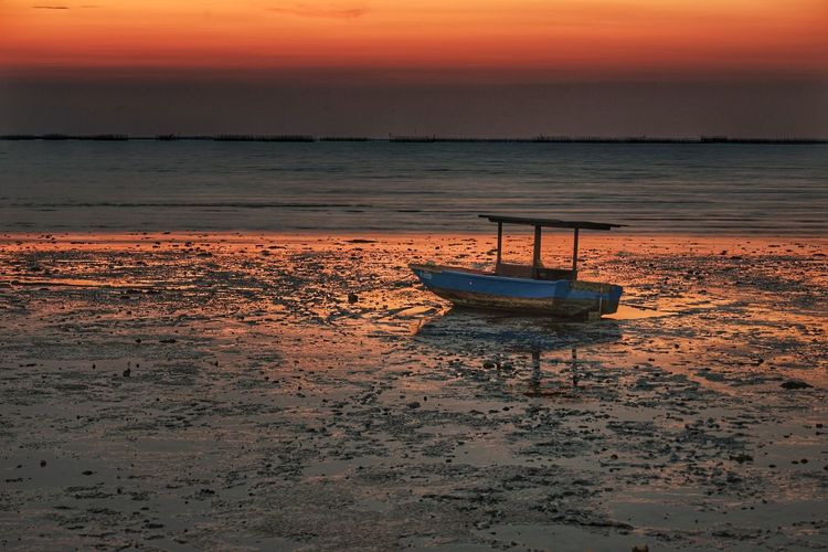 a boat Water Low Tide Sea Nautical Vessel Sunset Beach Sand Red Summer Reflection Dramatic Sky Seascape