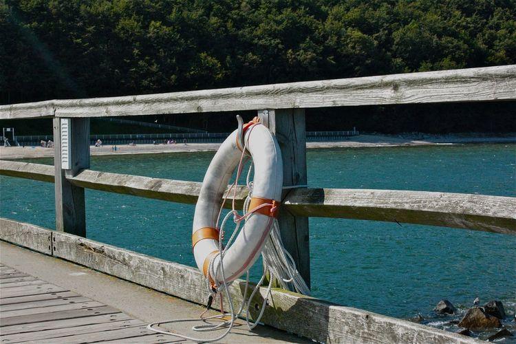Life belt hanging on pier railing over sea