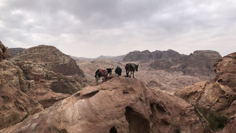 Group of people on rock formation against sky in the desert of giordania