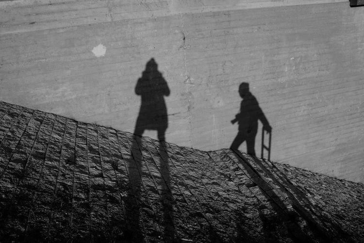Shadow of people walking on wall
