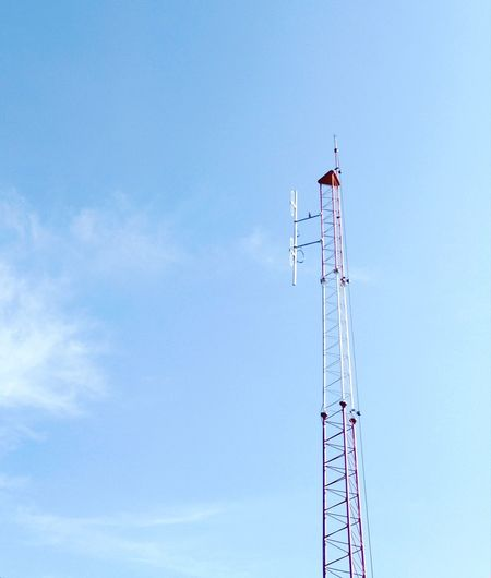 Low angle view of communications tower against blue sky