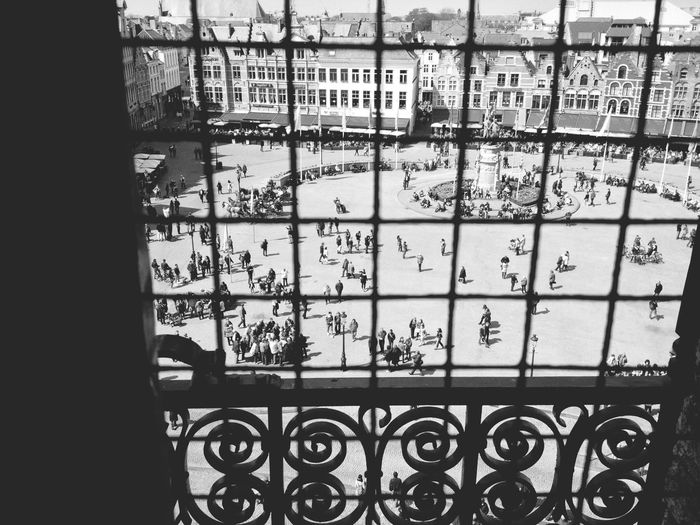 High angle view of people on town square seen through window