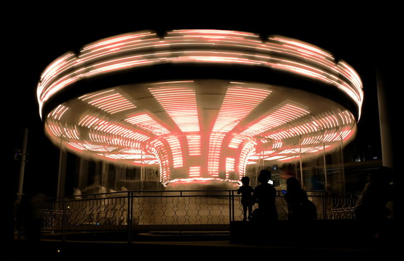 Illuminated carousel or merry-go-round with motion blur at night Illuminated Amusement Park Amusement Park Ride Night Leisure Activity Blurred Motion Long Exposure Carousel Spinning Speed Light Merry-go-round People Silhouette