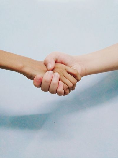 Cropped image of people shaking hands by wall