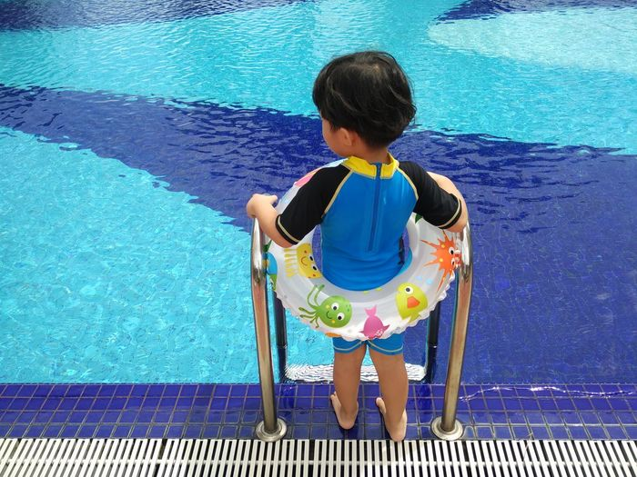 Rear view of girl in inflatable ring standing on poolside