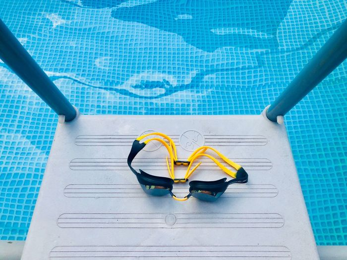 High angle view of goggles on ladder by swimming pool