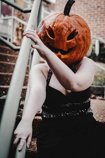 Portrait of woman wearing a pumpkin head