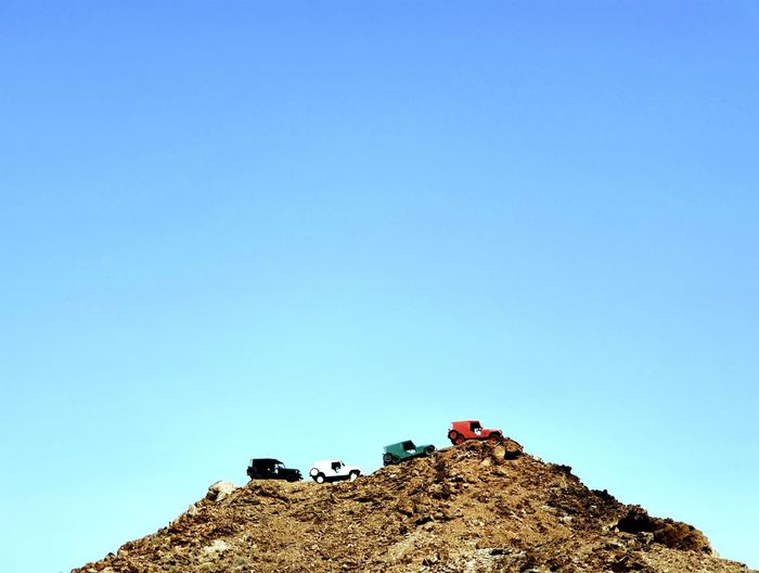 Low angle view of people on rocks against clear blue sky