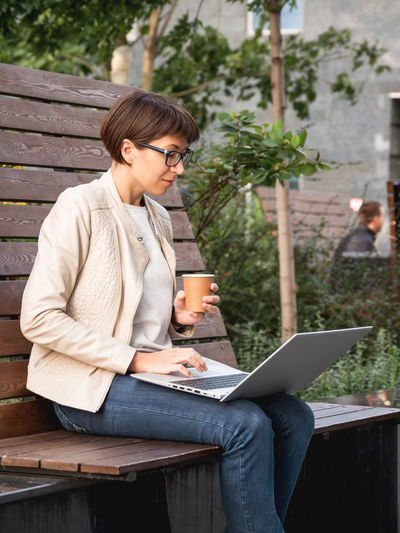 Freelance business woman sits in park with laptop,cup of coffee.urban lifestyle.working remotely.