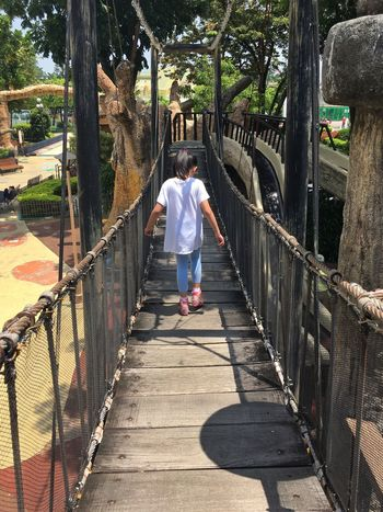 Scared of hanging bridge Full Length Real People Rear View One Person Lifestyles Walking Women Men Leisure Activity Tree Day Outdoors The Way Forward Built Structure Architecture People Playground Bridge Wooden Walking