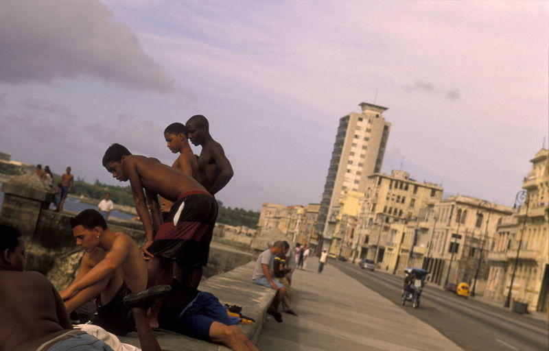 Tilt Image Of People On Shore By Street Against Sky