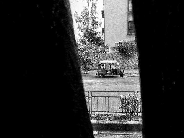 Road by buildings seen through window