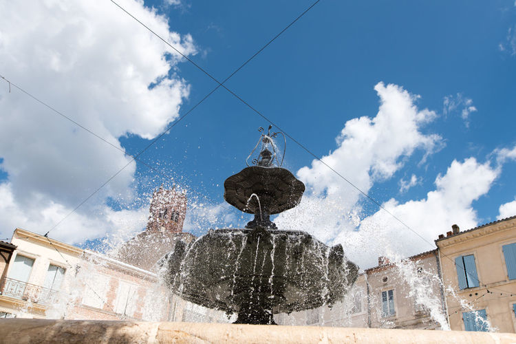 Low angle view of fountain against buildings in city