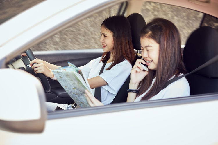 Vacation time and travel, beautiful young women cheerful travels together for a relaxing holiday. And the laughter in the car. Finding directions by map. Car Mode Of Transportation Motor Vehicle Transportation Travel Women Vehicle Interior Adult Sitting Real People Land Vehicle Lifestyles Young Women People Two People Indoors  Young Adult Car Interior Holding Casual Clothing Hairstyle